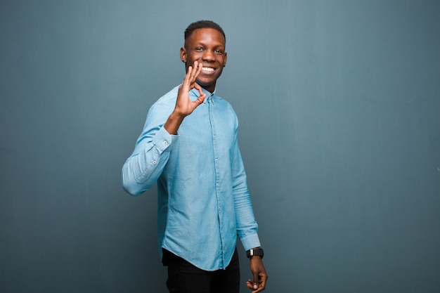 若いアフリカ系アメリカ人の黒人男性が幸せ、リラックス、満足を感じ、承認のジェスチャーで承認を示し、グランジの壁に笑みを浮かべて