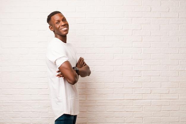 若いアフリカ系アメリカ人の黒人男性が喜んで笑顔、幸せ、満足、リラックス、腕を組んで、レンガの壁の側にいる