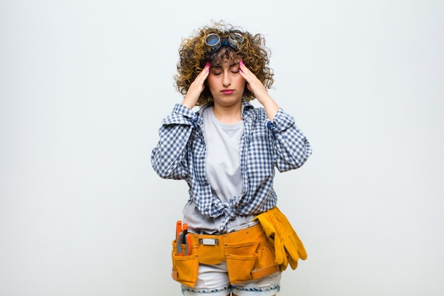 集中して思慮深くインスピレーションを得た若い家政婦女性ブレーンストーミングと白い壁の額に手で想像