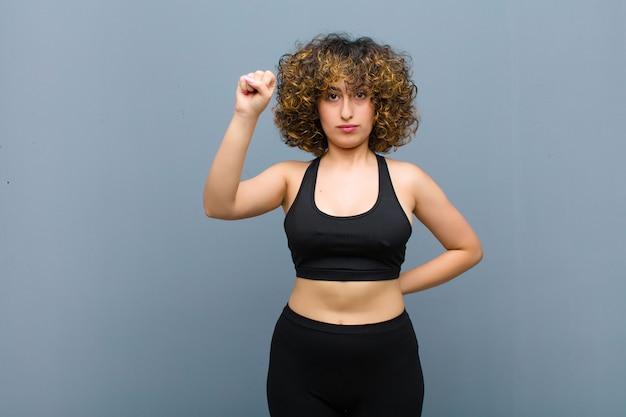灰色の壁で深刻な、強くて反抗的な、拳を上げる、抗議または革命のために戦う若いスポーツ女性