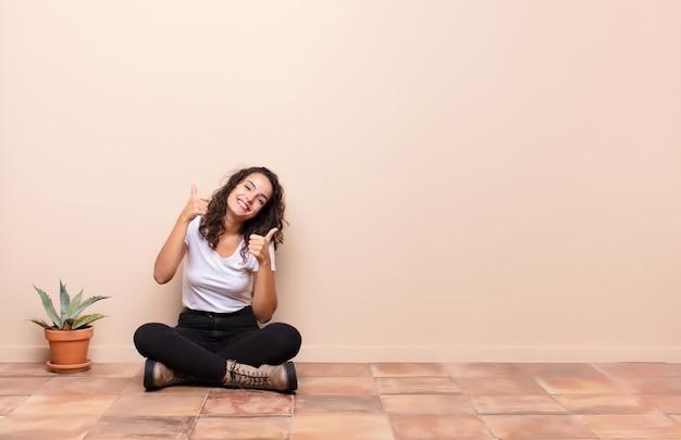 テラスの床に座っている両方の親指で、幸せ、肯定的、自信を持って、成功を広く見ている笑顔の若い女性