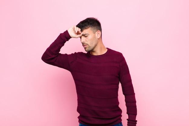ストレス、疲れ、欲求不満を探している若いハンサムな男、額から汗を乾燥、絶望的でピンクの壁に疲れ果てた
