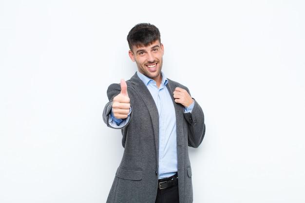 若いハンサムな男が誇りに思って、のんき、自信、幸せ、白い壁に対して親指で積極的に笑顔を感じて