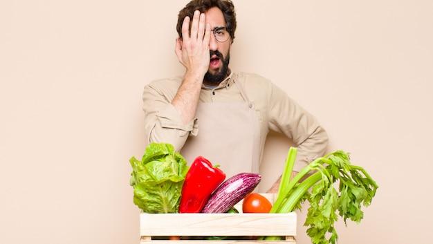 頭痛と片手で顔の半分を覆う、眠そうで退屈であくびをしている緑の食料品店の男性