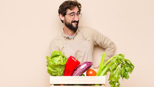 幸せでフレンドリーな笑顔と前向きな態度であなたに目をウインクしている緑の食料品店の男性