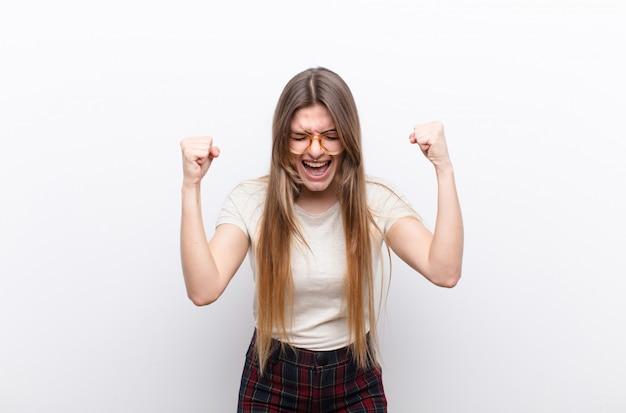 若いきれいな女性の幸せ、前向きで成功した、勝利、達成または白い壁に対する幸運を祝う