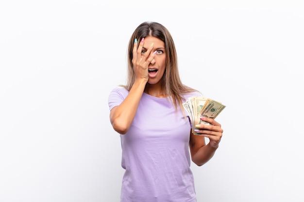 幸せ、驚き、誇りに思っている若いきれいな女性、紙幣で興奮し、驚いた表情で自己を指しています。
