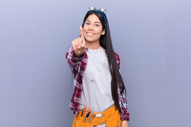 リーダーのように感じて、誇らしげに自信を持って自信を持って笑顔でナンバーワンのポーズをとる若いラテン女性