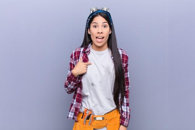 幸せ、誇りに思って驚いて、陽気に自己を指して、自信を持って高尚な感じの若いラテン女性