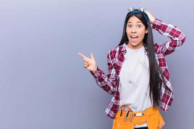 横向きのコピースペースを指す素晴らしいアイデアを実現する、笑って、幸せそうに見えて、前向きで、驚いて若いラテン女性