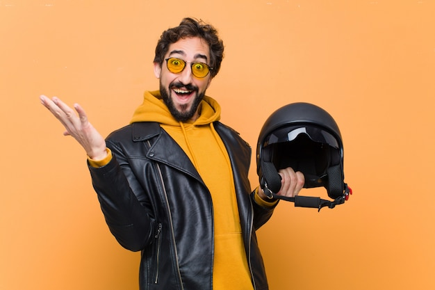 若い狂気のクールな男のライダー、バイクのヘルメットを握っています。