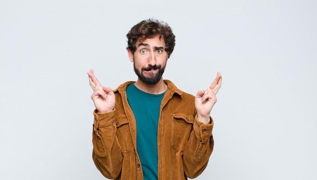心配そうに指を交差し、平らな壁に対して心配そうな顔つきで幸運を期待して若いハンサムな男
