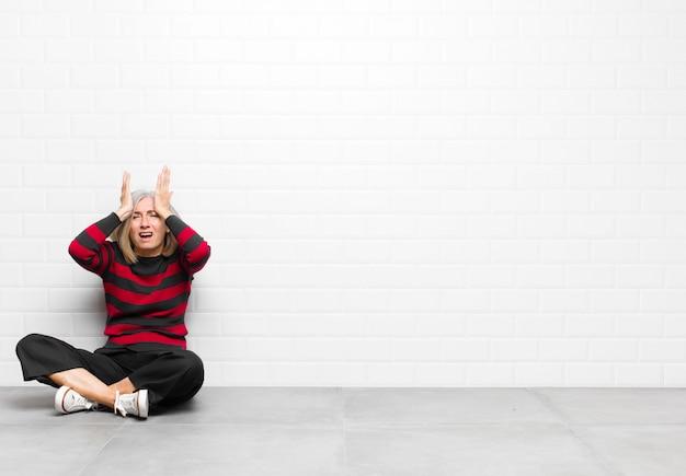 ストレスや不安を感じ、落ち込んでいて頭痛で欲求不満を感じ、両手を頭に上げているシニアまたは中年のきれいな女性