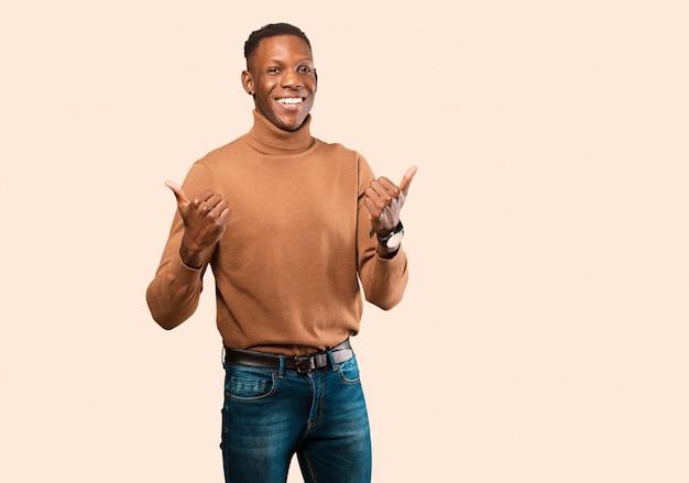 若いアフリカ系アメリカ人の黒人男性が嬉しそうに笑って幸せそうに見えて、ベージュの壁に対して両方の親指で屈託のない、肯定的な感じ