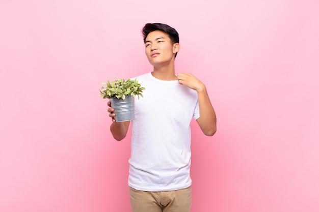 若い日本人男性がストレス、不安、疲れ、欲求不満を感じ、シャツの首を引っ張って、植物を抱える問題に不満を感じている