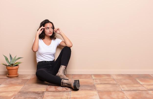 若いきれいな女性が混乱したり疑問を感じたり、アイデアに集中したり、一生懸命考えたり、テラスの床に座っている側にスペースをコピーしたりすることを探している