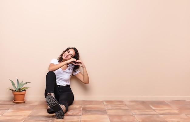 若いきれいな女性の笑顔と幸せ、かわいい、ロマンチックな愛の気持ちで、テラスの床に座っている両手でハートの形を作る