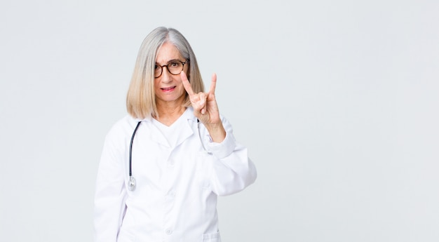 中年の医師の女性が幸せで、楽しく、自信を持って、前向きで反抗的で、手でロックまたはヘビーメタルのサインを作る