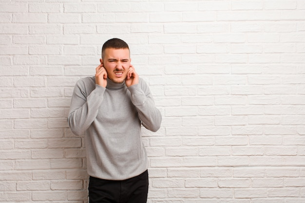 怒っている、ストレス、イライラ、ハンサムな若者、両耳をフラットな壁に聞こえないノイズ、音、または大音量の音楽にカバー