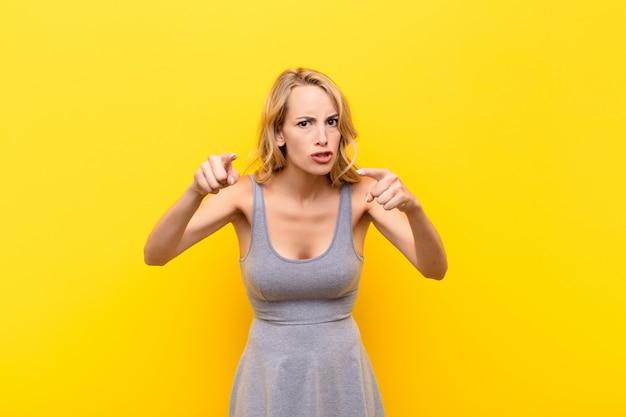 両方の指と怒りの表現で前方を指している、オレンジ色の壁に対して義務を果たすように言っている若いブロンドの女性