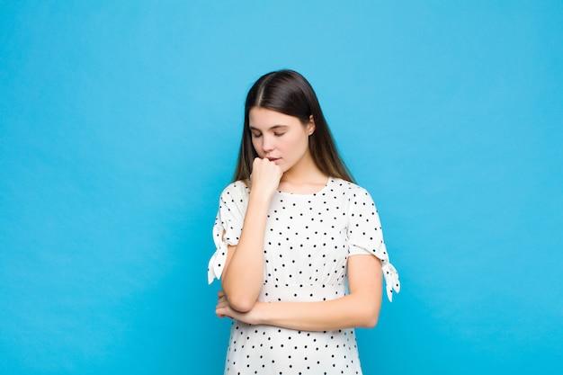 Молодая красивая женщина чувствует себя серьезной, задумчивой и обеспокоенной, глядя в сторону, прижавшись рукой подбородок к синей стене