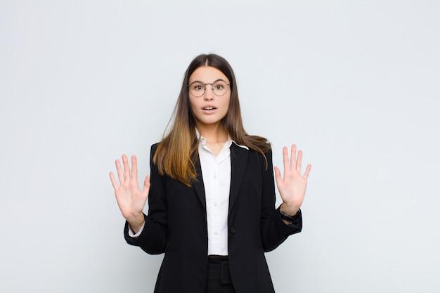 Молодая деловая женщина чувствует себя ошеломленной и напуганной, боится чего-то пугающего, с открытыми руками и говорит: держись подальше от белой стены