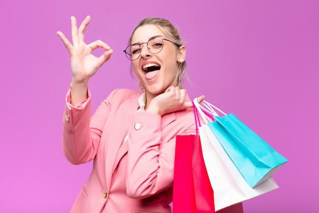 買い物袋を保持している若いかなりブロンドの女性