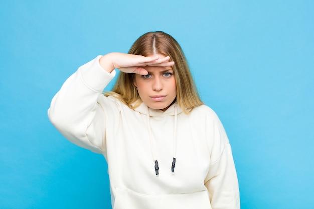 若いブロンドの女性が戸惑い、驚いて、遠くを見て、平らな壁を見て、検索する額に手で