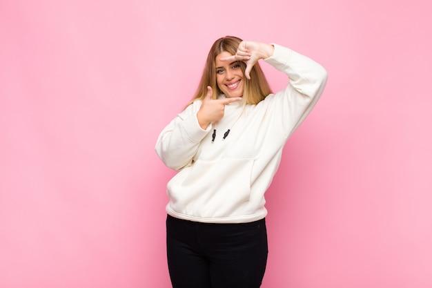 若いブロンドの女性は幸せ、フレンドリーでポジティブな感じ、笑顔、平らな壁に手で肖像画やフォトフレームを作る