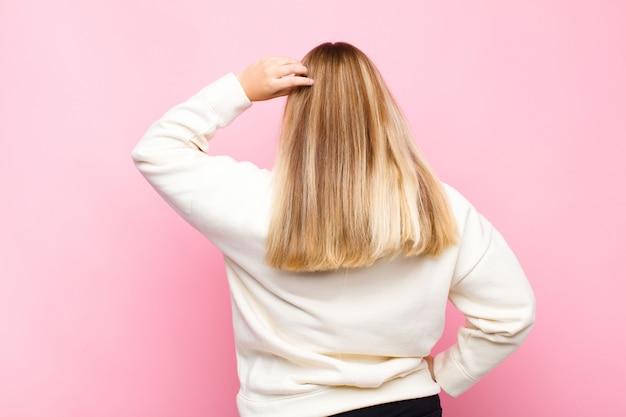 無知と混乱している若いブロンドの女性、解決策を考えて、腰に手と頭の上に他の人、フラットな壁に対して背面図
