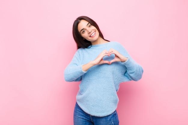 ピンクの壁に両手でハートの形を作る笑顔と幸せ、かわいい、ロマンチックな愛の若いきれいな女性
