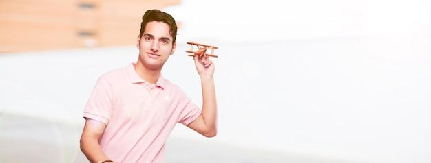 Молодой красивый загорелый человек с деревянный самолет