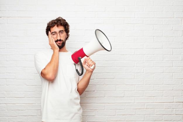 レンガの壁にメガホンを持つ若いクレイジーな男。