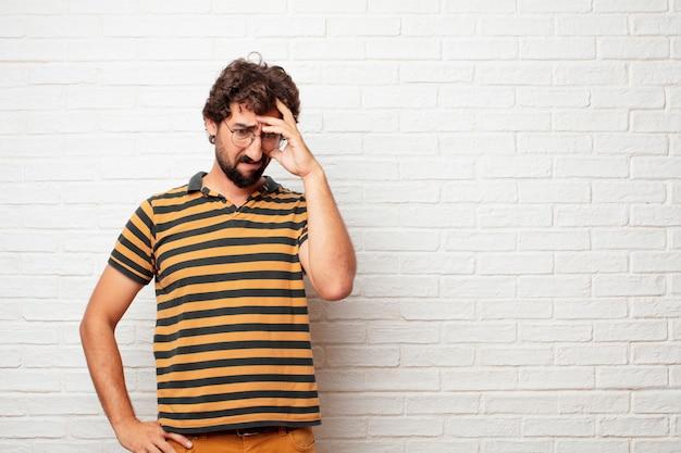 レンガの壁の背景に感情を身振りして表現する若い狂った、あるいは愚かな男