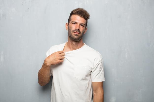 Молодой красивый мужчина с напряженным жестом, потливость и потянув рубашку шеи открытой, чувствуя себя подавленным.