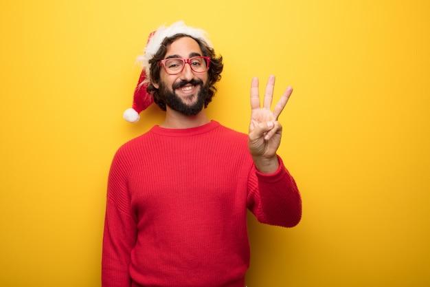 赤いメガネとサンタクロース帽子を身に着けている若い狂ったひげのある男