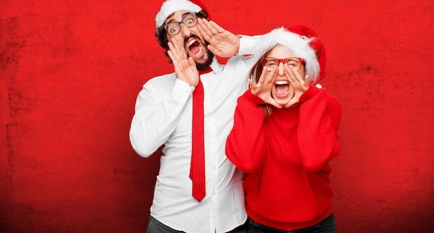 クリスマスのコンセプトを表現する若いカップル。カップルとさまざまな層の背景