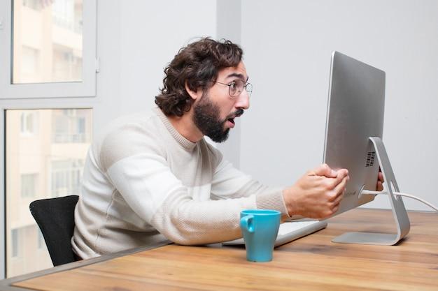 彼のコンピュータで働く若いひげの狂ったフリーランサー