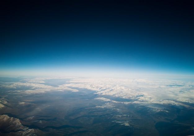 青空と雪が降った山々の景色。惑星地球概念