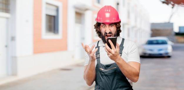 携帯電話を持つ若い男労働者