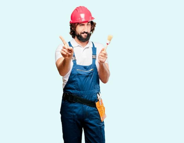 ペイントブラシを持つ若い男労働者