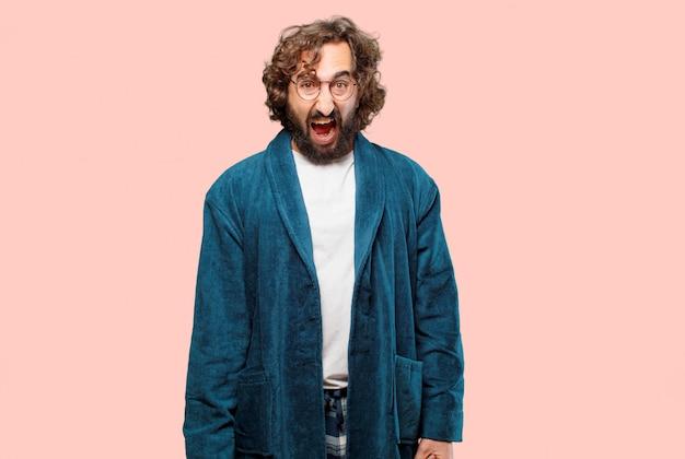 バスローブの夜のスーツを着ている若い男が怒っているポーズ