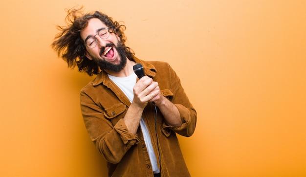Молодой человек с сумасшедшими волосами в движении поет