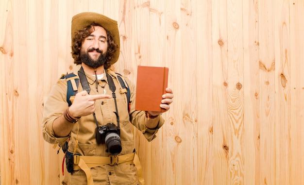 麦わら帽子と木製の背景にバックパックの若いクレイジーエクスプローラー