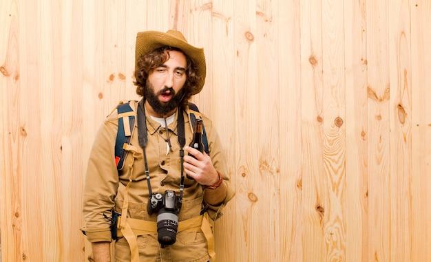 Молодой сумасшедший исследователь с соломенной шляпой и рюкзаком на фоне дерева