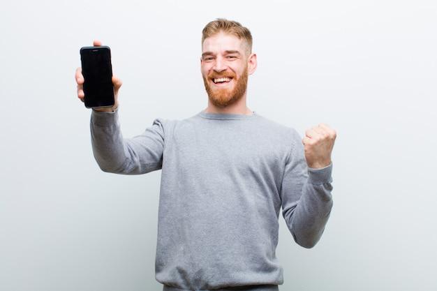 Молодой рыжий мужчина со смартфоном на белом фоне