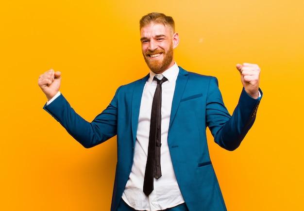 意気揚々と叫んで、興奮して、幸せで、驚きの勝者のように見える若い赤ヘッド実業家、オレンジ色の背景を祝う
