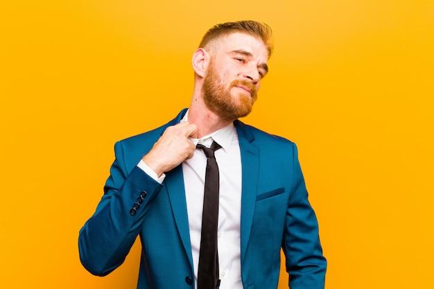 Молодой рыжий бизнесмен, чувствуя стресс, беспокойство, усталость и разочарование, потянув рубашку шею, глядя разочарованы проблемой на оранжевом фоне