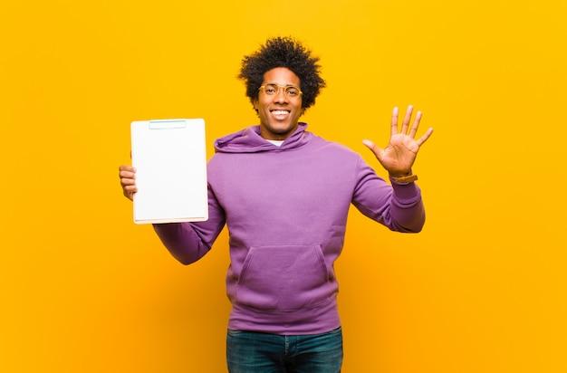 オレンジ色の背景に対して若いアフリカ系アメリカ人