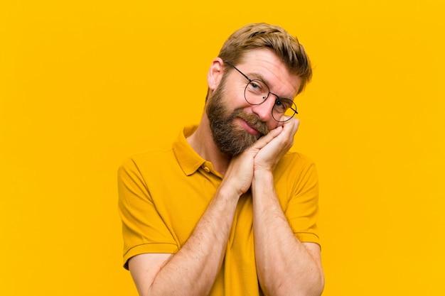 オレンジ色の壁に対して顔の横にある手でロマンチックに笑顔で愛と感じ、かわいい、愛らしい、幸せな探している若い金髪男